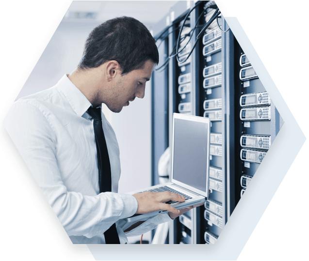 Man Working on Laptop in Server Room