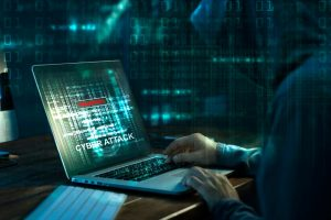 Hooded man on laptop with cyberattack on screen